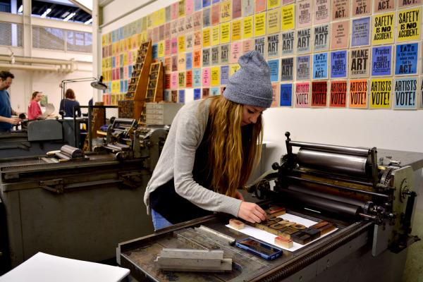 A VCD student working with moveable type on a press.