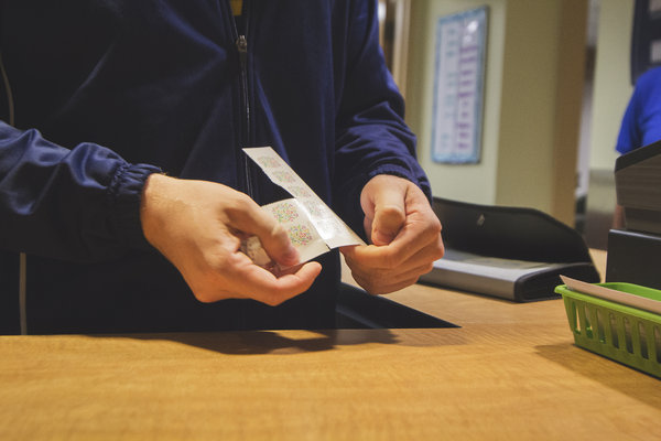A student tears off a section of stamps at the Student Center Post Office