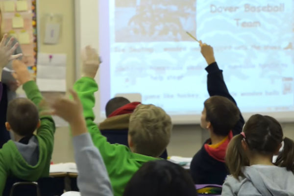 Children raise their hands in a classroom discussion