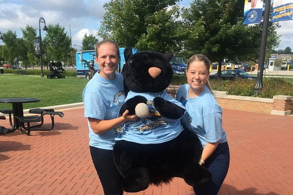 Students with a large stuffed black squirrel.