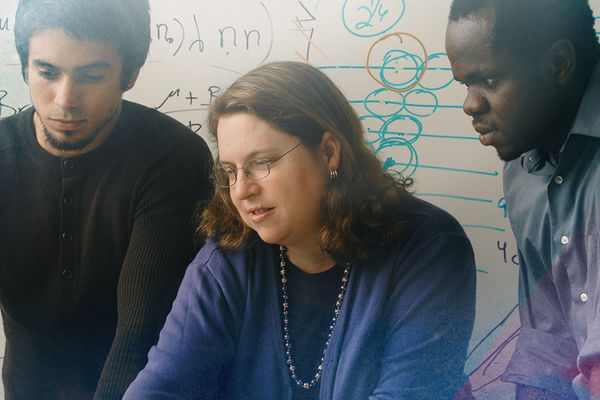 A professor helping two students