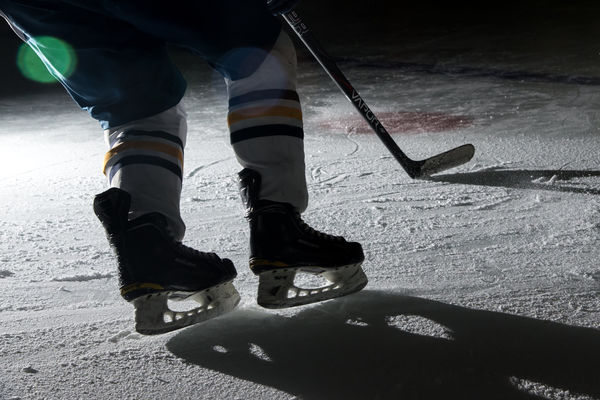 A hockey player skates across the ice under a spotlight.