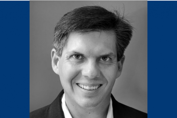 Headshot of Robert Nowatzki on a blue background