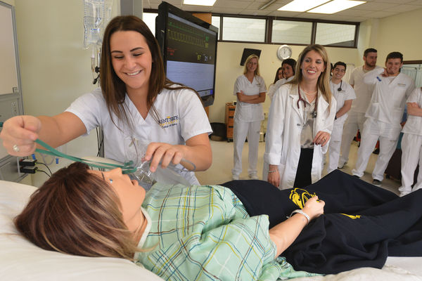 A Kent State nursing student practices putting an oxygen mask on a patient simulator