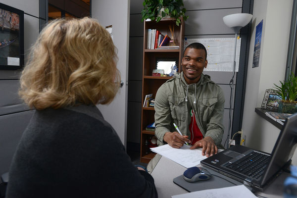 A student in the Colelge of Communication and Information works with his advisor to chart his educational path.