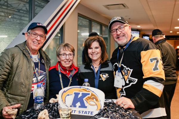 Group of Kent State alumni, wearing KSU gear, smiling for the camera