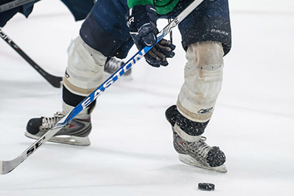A hockey player positions his hockey stick to hit a puck on the ground as they skate across the ice at the Kent State Ice Arena.