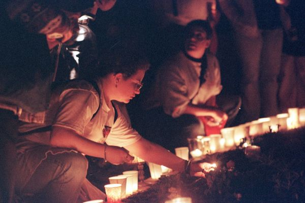 A girl lighting a candle during a May 4 Commemoration