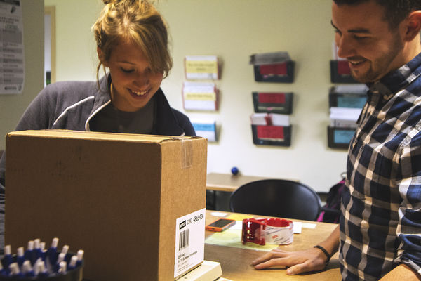 A student picks up a package at the Student Center Post Office