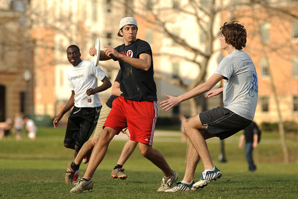A group of male students play a game of frisbee on the lawn outside of Tri Towers.