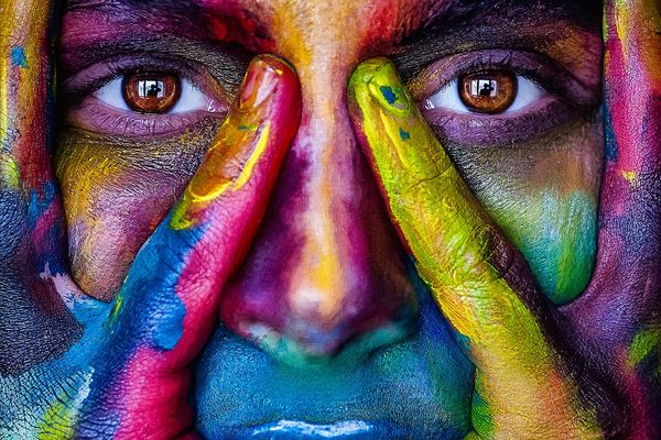 A woman holding her hands over her face, both of which are painted in rainbow colors