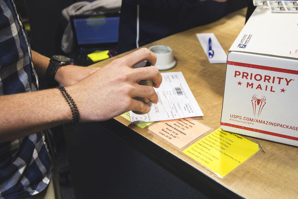 A student stamps a mail form for international delivery