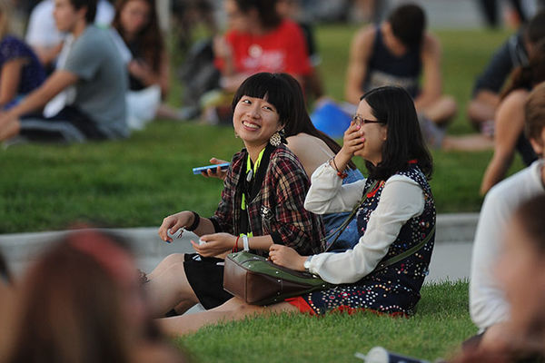 A group of female students share a laugh while sitting on the grass in the late afternoon.