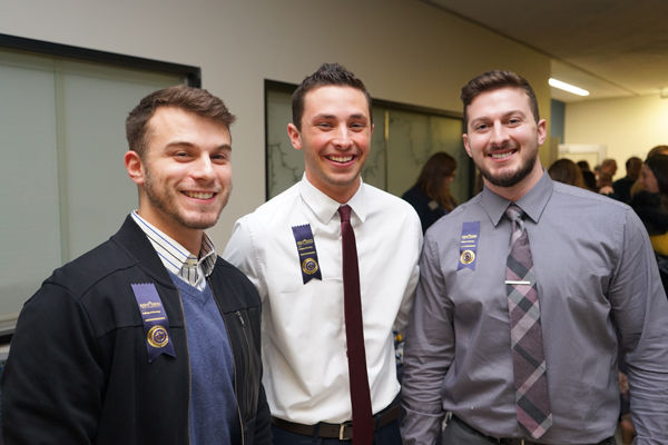 Three male nursing students celebrate the completion of their degrees following their Convocation pinning ceremony