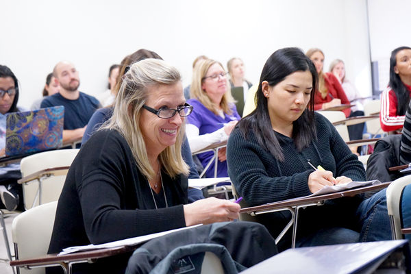 A classroom of adult students listen intently to a nursing lecture