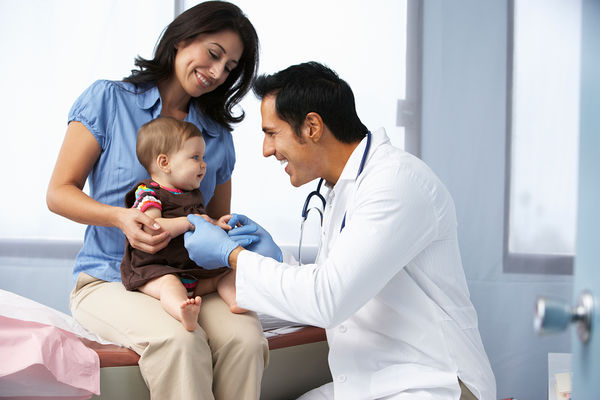 A male Pediatric Nurse Practitioner examines a baby who is sitting in her mother's lap