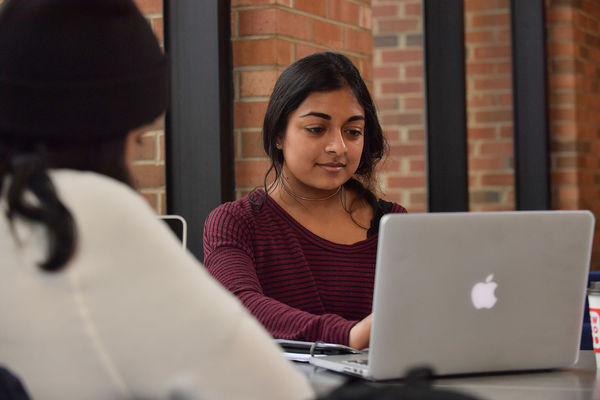 A student works on classwork on her laptop