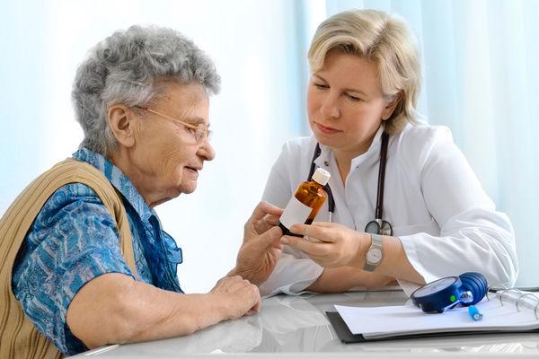 A Nurse Practitioner shows an elderly patient her medicine dosage