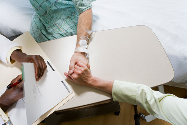 A man in a hospital bed, his hand being held by a woman sitting across from him, and a Nurse Practitioner checking his chart
