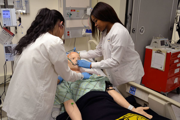 Two nursing students learning by interacting with a simulation mannequin