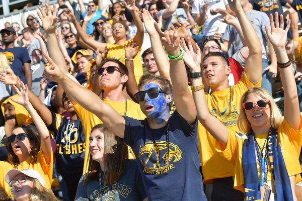 Kent State alumni and students, wearing blue and gold gear, holding their hands up in the air