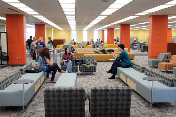 A group of female students sit on sofas located on the fourth floor of the Library.  Other students can be seen sitting and working on sofas behind them.