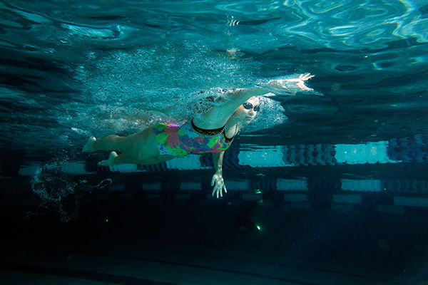 A female swimmer practices her stroke in the Student Recreation and Wellness Center lap pool.