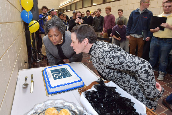President Warren and Dean Broome blow out candles for the College of Nursing's 50th birthday part on January 23, 2017
